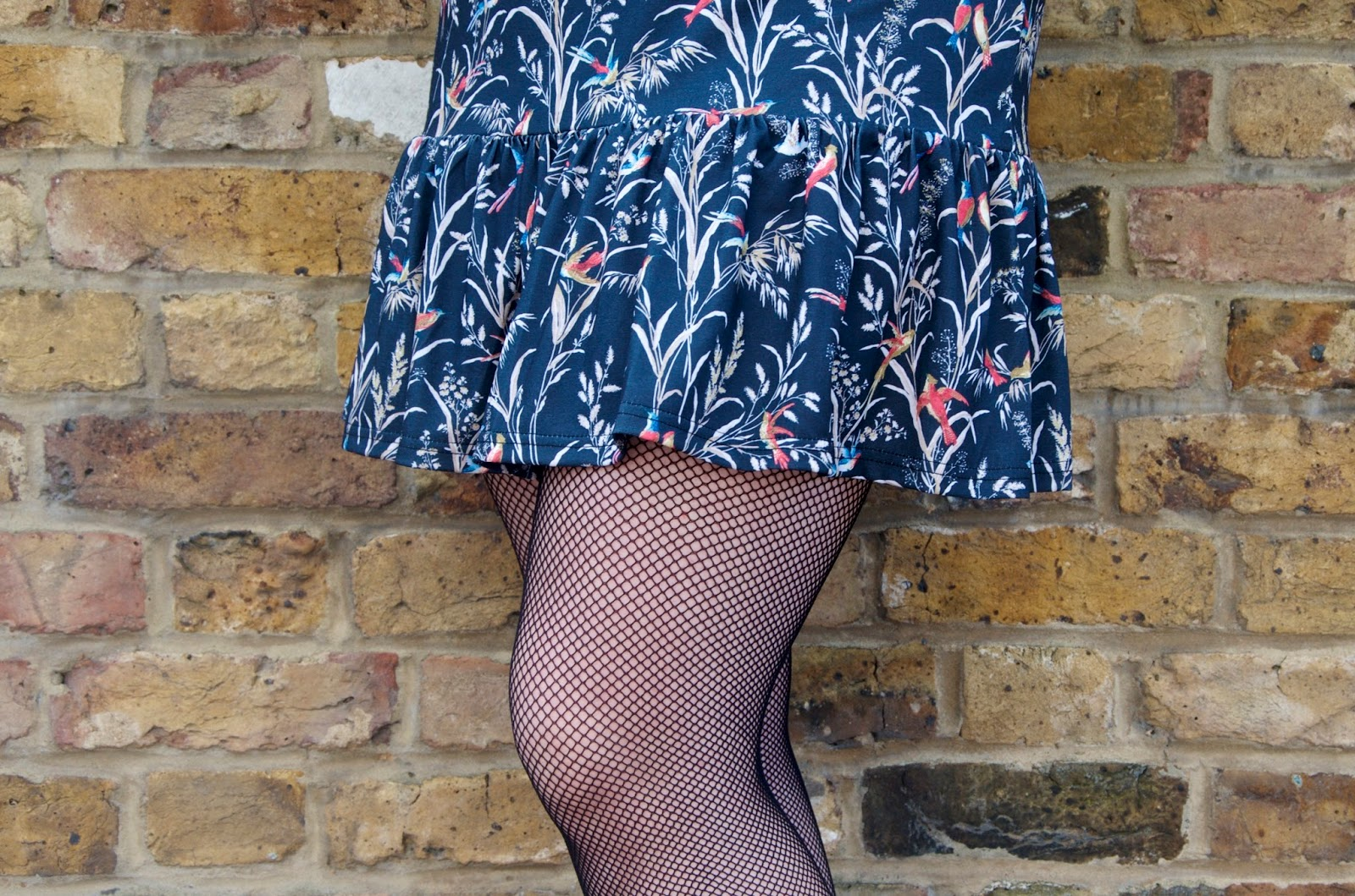 Bird print ruffle dress and fishnet tights