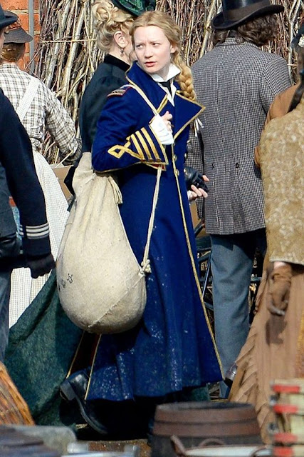 Alice andando na rua carragando um pacote