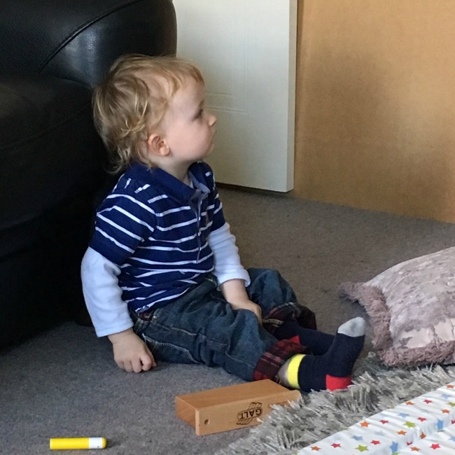 toddler sat on floor staring blankly, looks like he's about to nod off