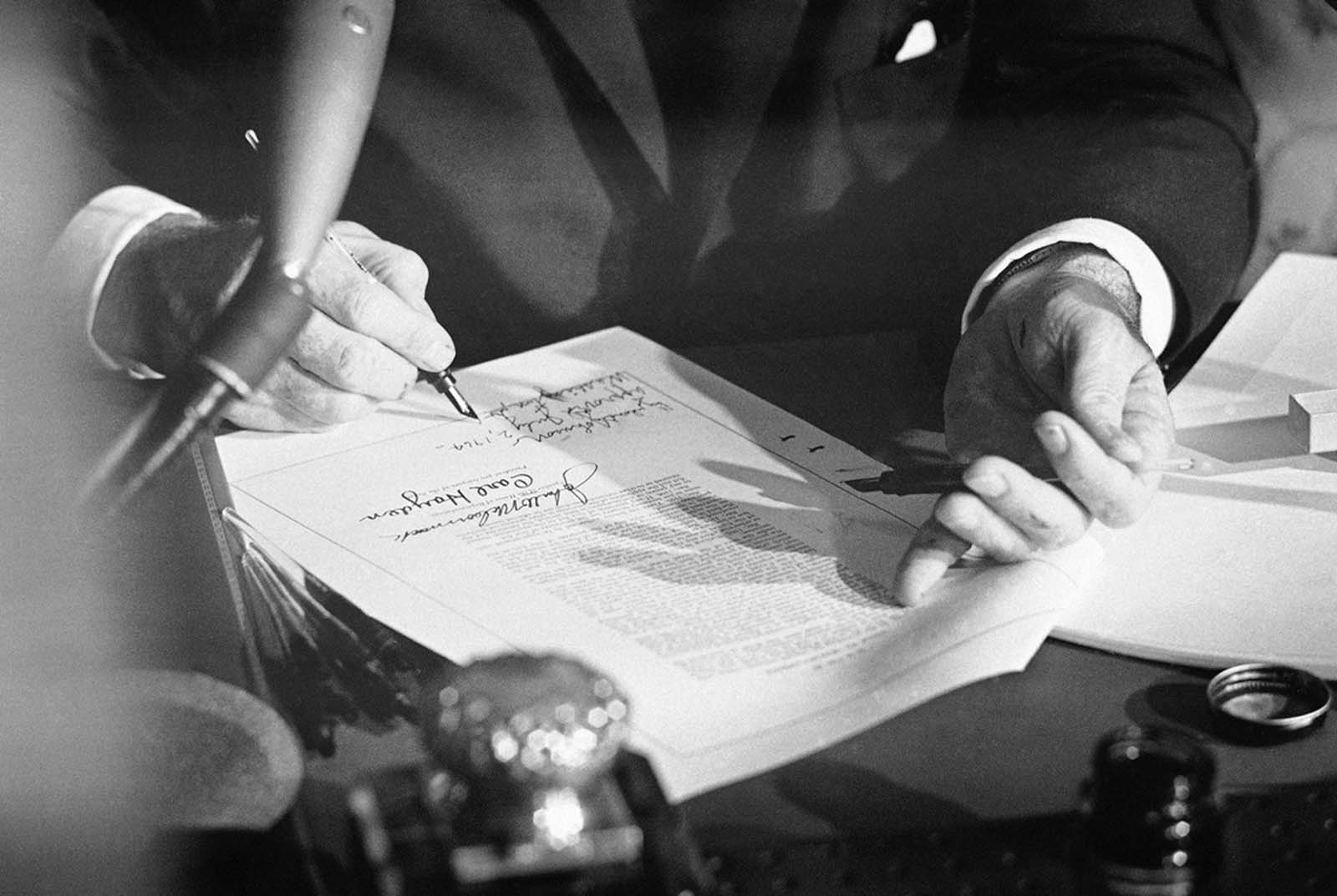 President Lyndon Johnson signs the Civil Rights Bill in the East Room of the White House in Washington on July 2, 1964. The law outlawed discrimination based on race, color, religion, sex, or national origin, and ended unequal application of voter registration requirements and racial segregation in schools, at the workplace and by facilities that served the general public.