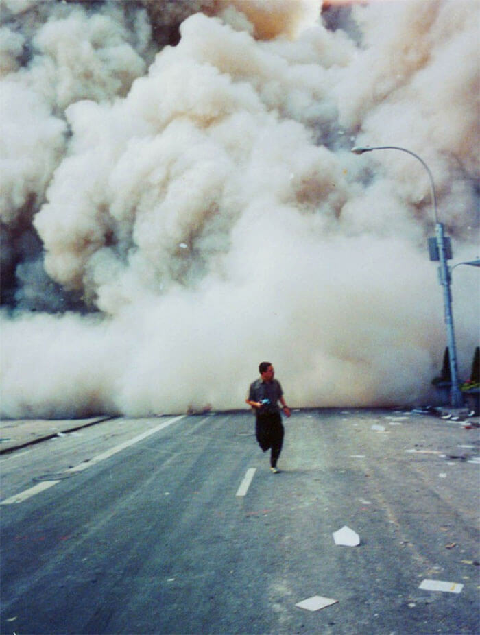18 Rare Historical 9/11 Photos That You Most Possibly Haven't Seen Before - A Lone Man Runs Down Broadway As A Smoke And Dust Cloud Comes Up The Street From The Collapsing World Trade Center Buildings In New York September 11, 2001