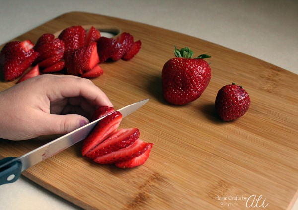 child slicing red strawberries for food preparation