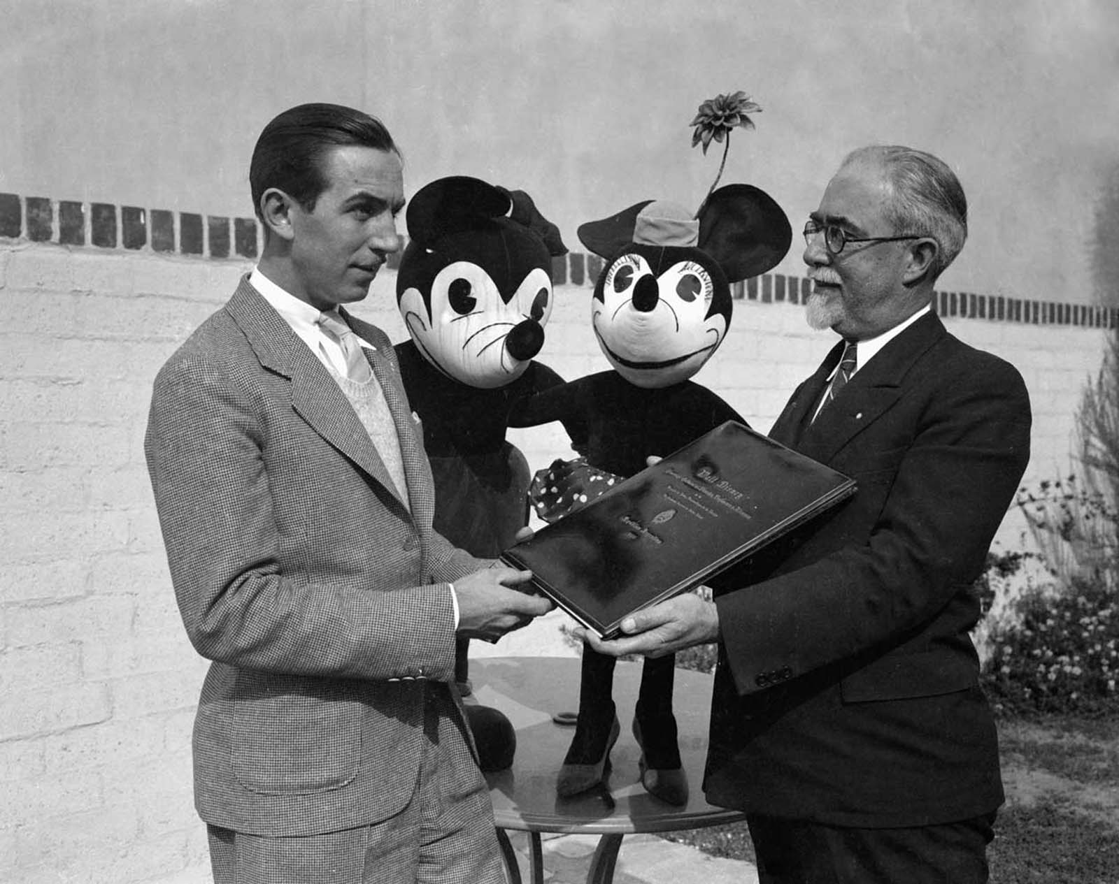 Walt Disney presented with a diploma of commendation from the National Academy of Fine Arts of Buenos Aires, Argentina. Mickey and Minnie look on.
