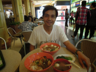 A travel blogger eating hot noodle soup at the food hall of The Venetian Hotel in Macao