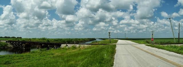 Miami Canal y la calle en el tramo asfaltado y un cruce ferroviario