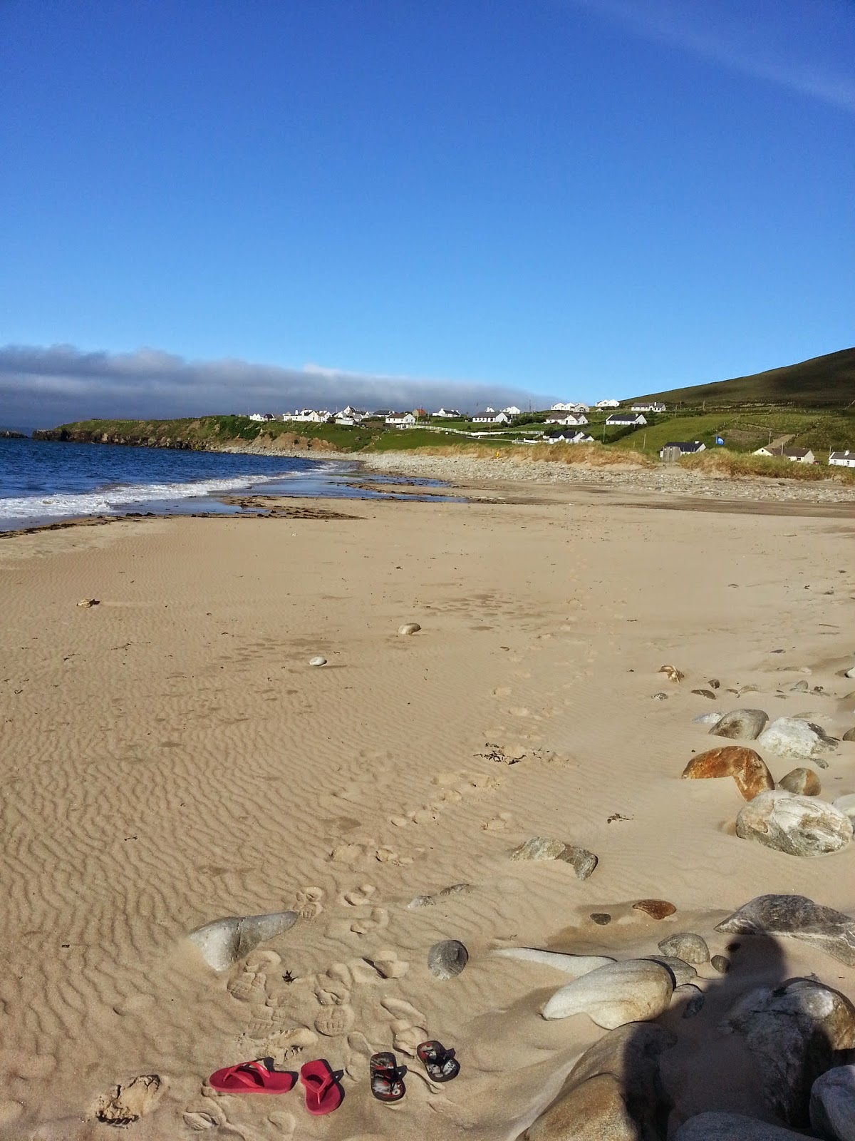 pristine beach on achill island with flips flops to the forefront and beautiful golden sand and the atlantic ocean