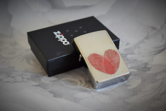 A zippo box with a silver lighter leaning against it imprinted with a heart made from two fingerprints.