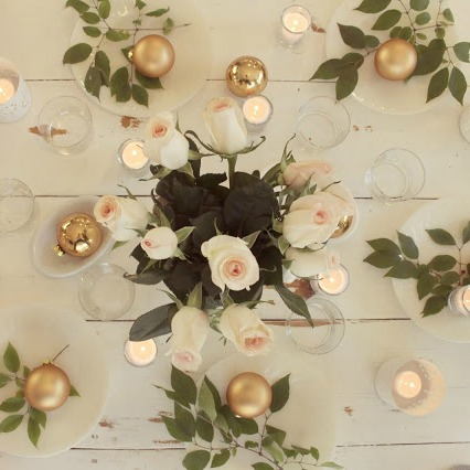 Christmas tablescape with blush roses, gold ornaments, fresh branches, and white plates on white farmhouse table by Hello Lovely Studio