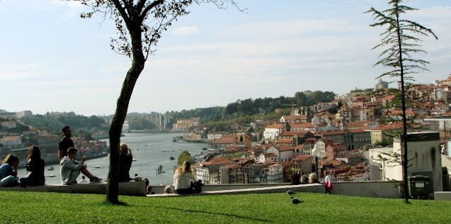 Pessoas sentadas no Jardim do MOrro apreciando a vista para o rio Douro e a cidade do Porto