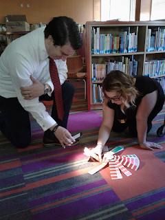 A man and a woman comparing color palettes to the Little Falls Library carpet.