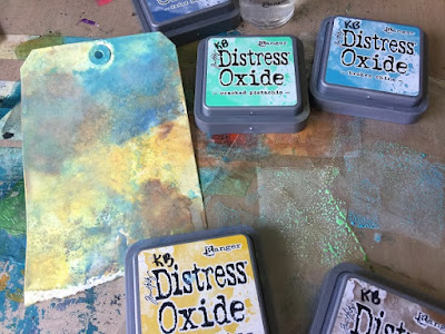 A tag with distress oxide colors marbling browns, yellows & blues, so grungy.