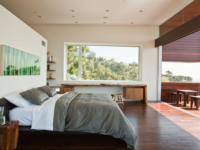 Picture of king sized bed and long wooden desk by the window in the Sunset Plaza Drive Residence bedroom