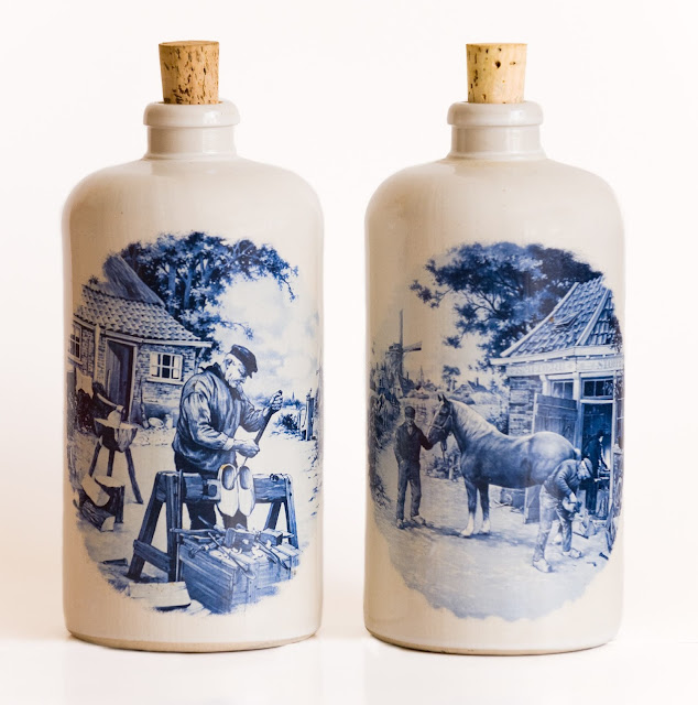 Two large Delft stoneware jugs with Dutch scenes in blue and white, and corked tops.