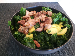 a bowl with kale salad, mangos, and jerk chicken