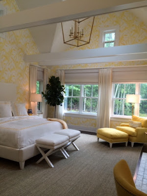 Large, bright, pale yellow bedroom with white and yellow furnishings at designer showhouse