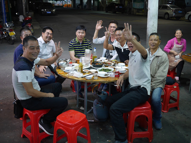 group of men eating and drinking at an outdoor table