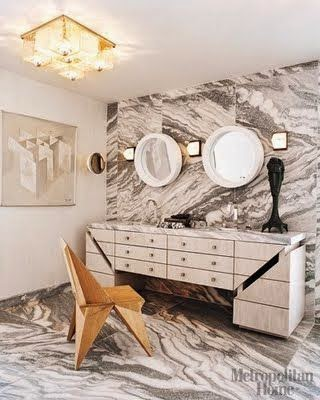Bathroom witn grey marble with heavily veins on floor and fron wall, rounded mirrors, two sinks and a dresser for vanity