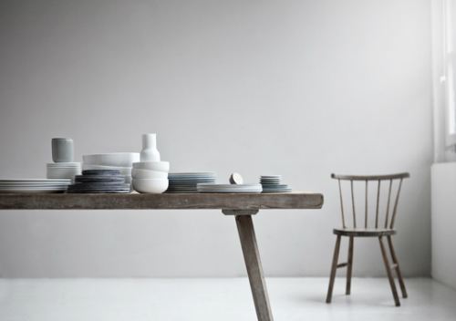 Auf einem rustikalen Tisch stehen aufeinander gestapelt Teller und Schalen