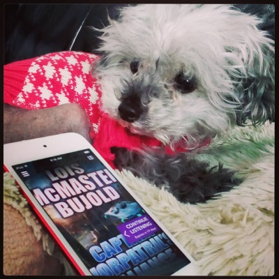 Murchie crouches on his fuzzy pillow. He wears his pink and white sweater and has his head twisted to look at something behind him. Beside him is a white-bordered iPod with the cover of Captain Vorpatril's Alliance on its screen. The cover features a futuristic silver ship hovering over a city, sandwiched between the author's name and the title in large block letters.