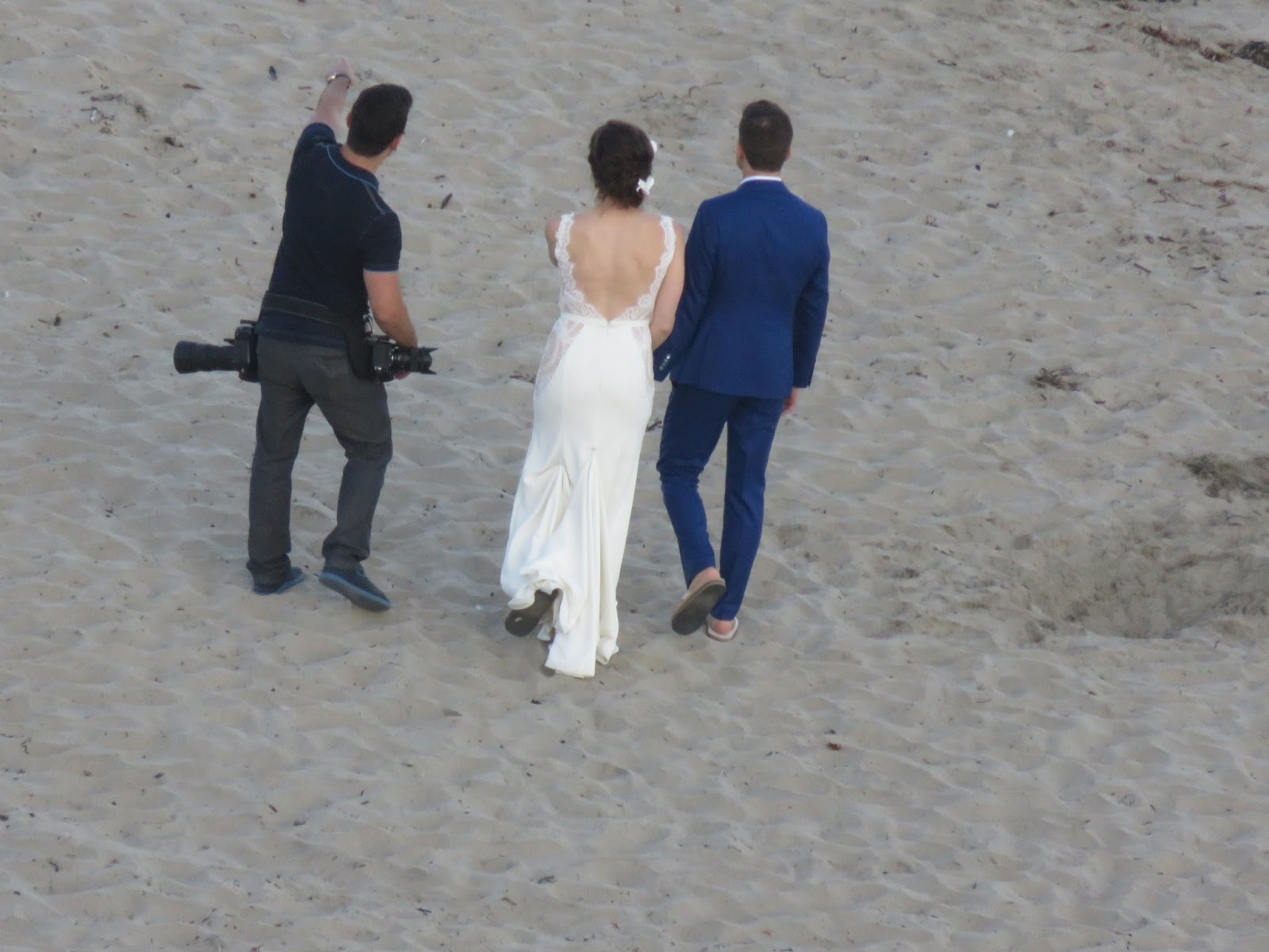 Bride and groom walk on beach.
