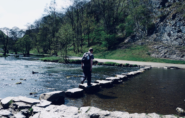 A man walking across stepping stones crossing a shallow river in Derbyshire