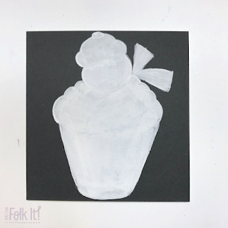 Painted white silhouette of the a snowman topped cupcake.