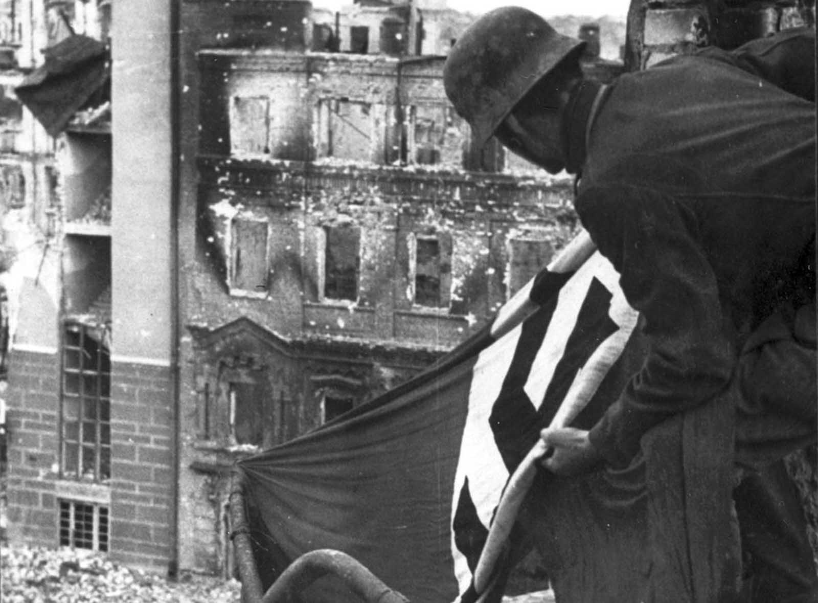 Sometime in the Autumn 1942, a German soldier hangs a Nazi flag from a building in downtown Stalingrad.