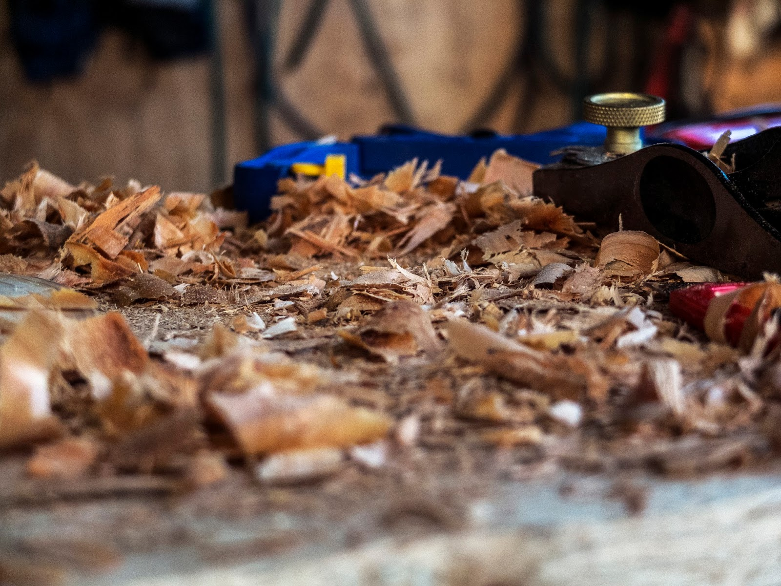 View of a woodworking bench with shavings and a wood plane.