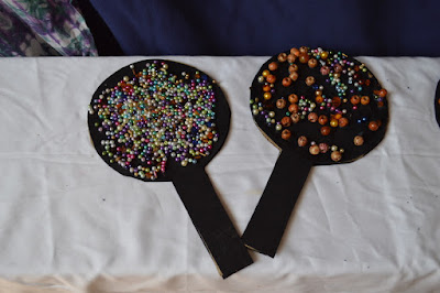 Two fans made from black cardboard with beads stuck on the top