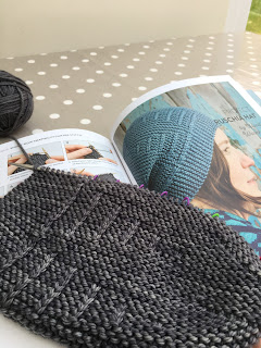 A knitted hat in progress and an open book