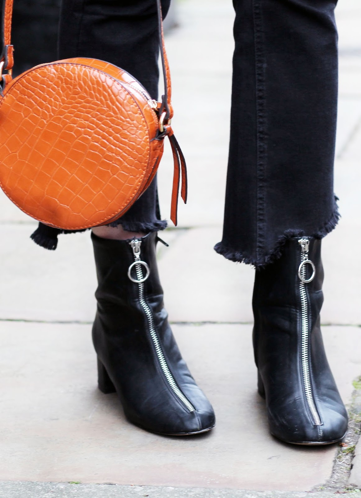 ASOS black zip up boots with ring pull detail, black crop kick flare jeans and burned orange mock croc bag