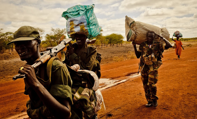 South Sudan Defense Forces soldiers and a woman carry their belongings along the road from Agok to Turalei South Sudan
