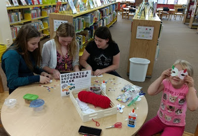 three teens and a younger child sit at a table decorating paper superhero masks, the youngest child is wearing the mask