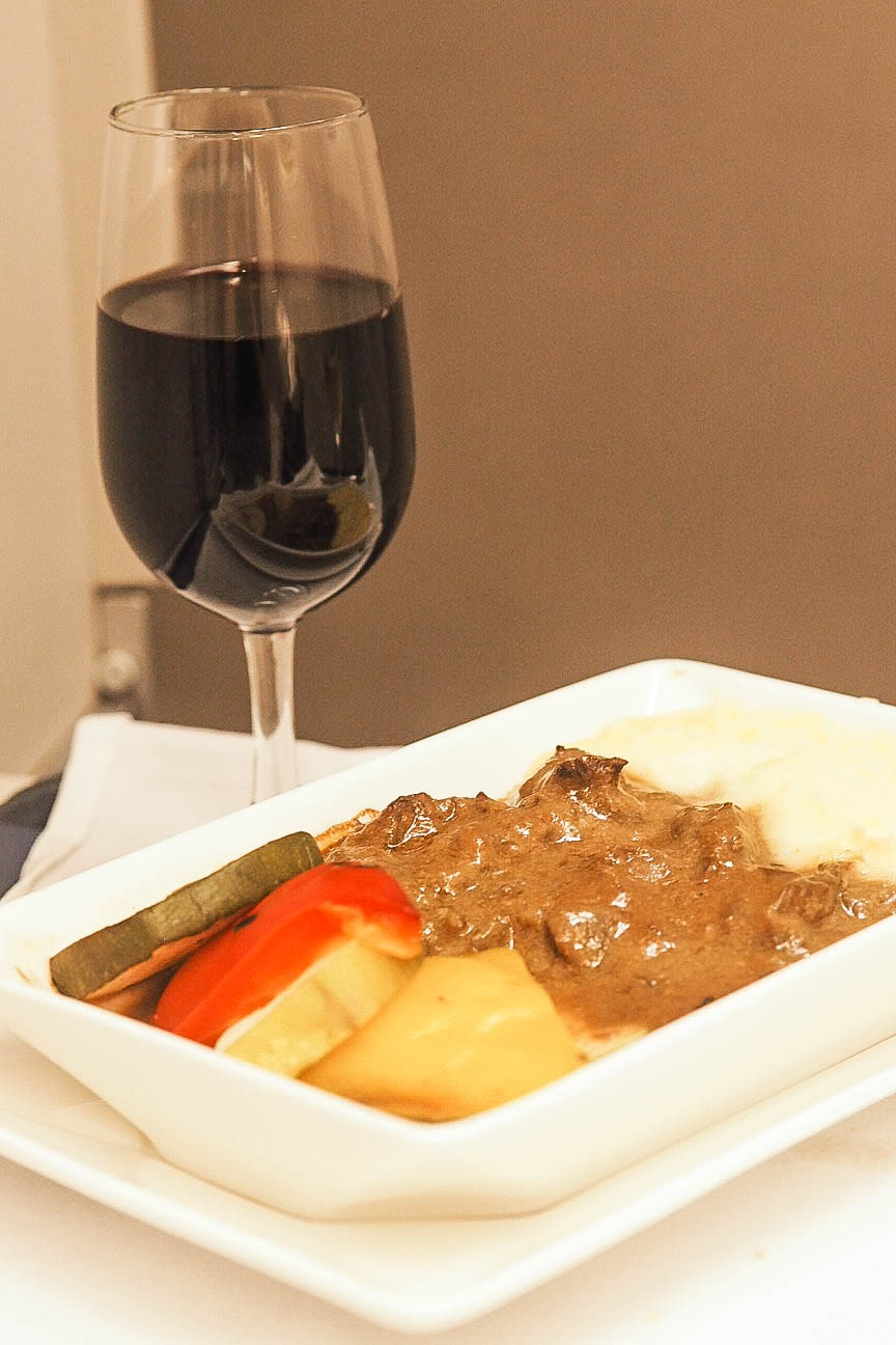 Slow-braised beef with creamy mustard sauce, mashed potatoes and grilled courgette, and a glass of red wine
