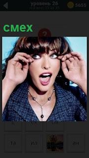 Девушка с длинными волосами выражает смех так, что потекли слезы из глаз которые она вытирает пальчиками