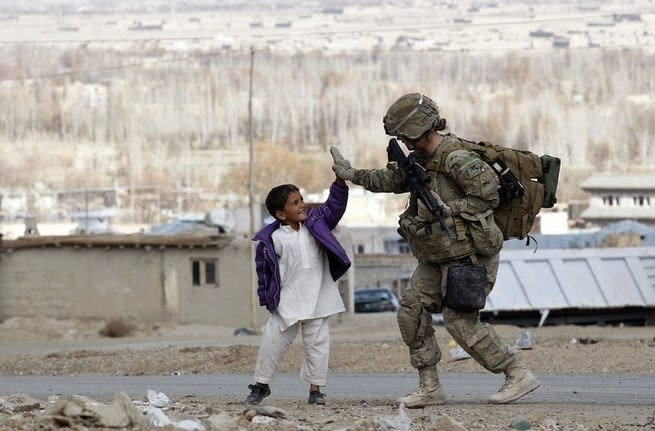 25 Photos Of People Who Will Inspire You - A U.S. Army soldier high fives a young boy in Afghanistan.