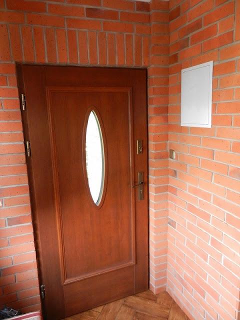 Drzwi wejściowe prowadzące do ceglanego ganku.