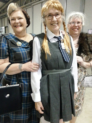 Two women dressed in 1940s outfits pose with a woman in a gym slip.