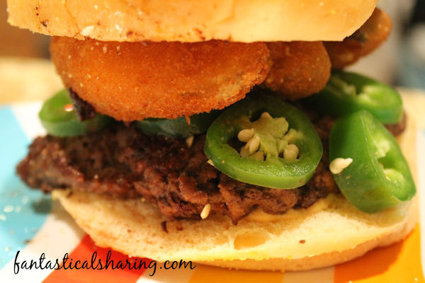 Hella-peno Burger | This copycat burger packs a punch because not only is it topped with sliced jalapenos - it has jalapeno poppers and salsa con queso on it too! #SundaySupper #copycat #burgers #recipe