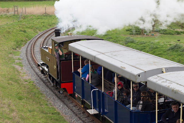 The steam train at ZSL Whipsnade Zoo pulling along carriages with people in