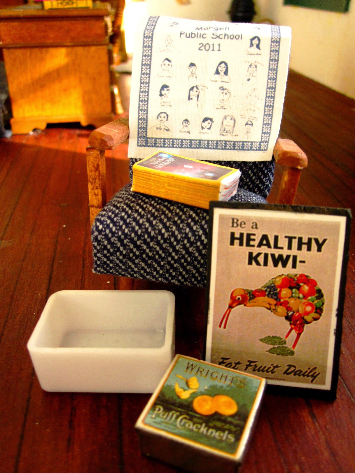 Collection of miniature items including a 1950s-style chair, a tea towel, a stack of old National Geographic magazines, a white plastic tub, a 'Be a health Kiwi' poster and an old biscuit tin.