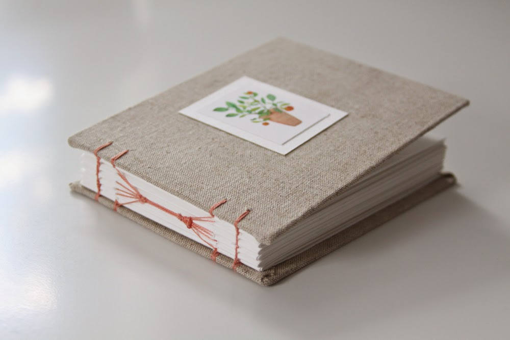 hand bound book with linen cover and potted orange tree illustration
