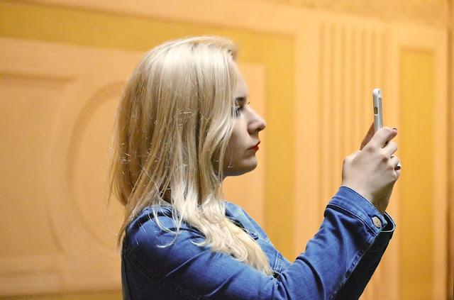 Blonde woman using instagram on her phone