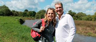Andrea Grießmann und Manes Meckenstock stehen auf einer Wiese, im Hintergund ist ein kleiner See oder Teich zu erkennen