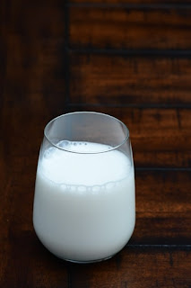 A small clear glass of milk