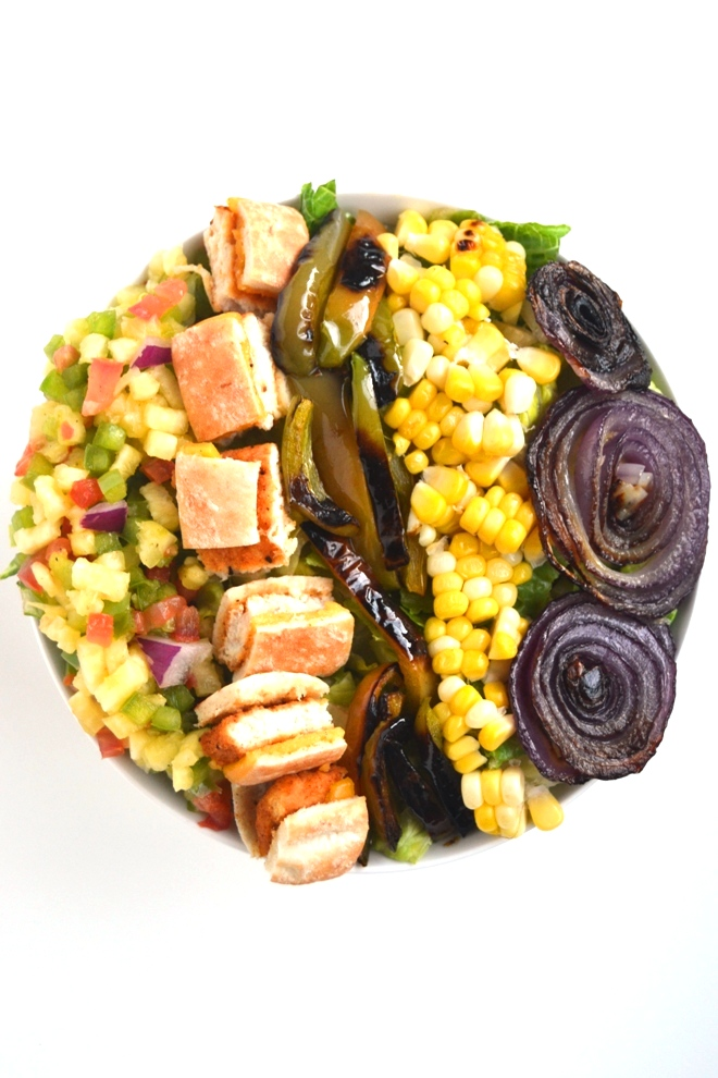 Pineapple Salsa Chicken Salad is loaded with homemade fresh pineapple salsa, grilled corn, peppers and onions, chicken and topped with a garlic lime vinaigrette! www.nutritionistreviews.com