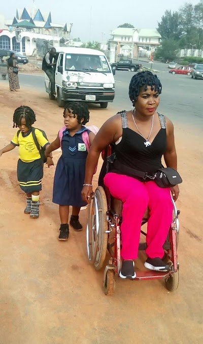 Touching Photo of a Physically challenged woman joyfully Taking her Kids to School, (photo)
