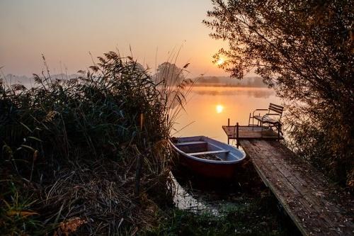 Barco na margem do lago, paisagem, pier ao amanhecer. #PraCegoVer