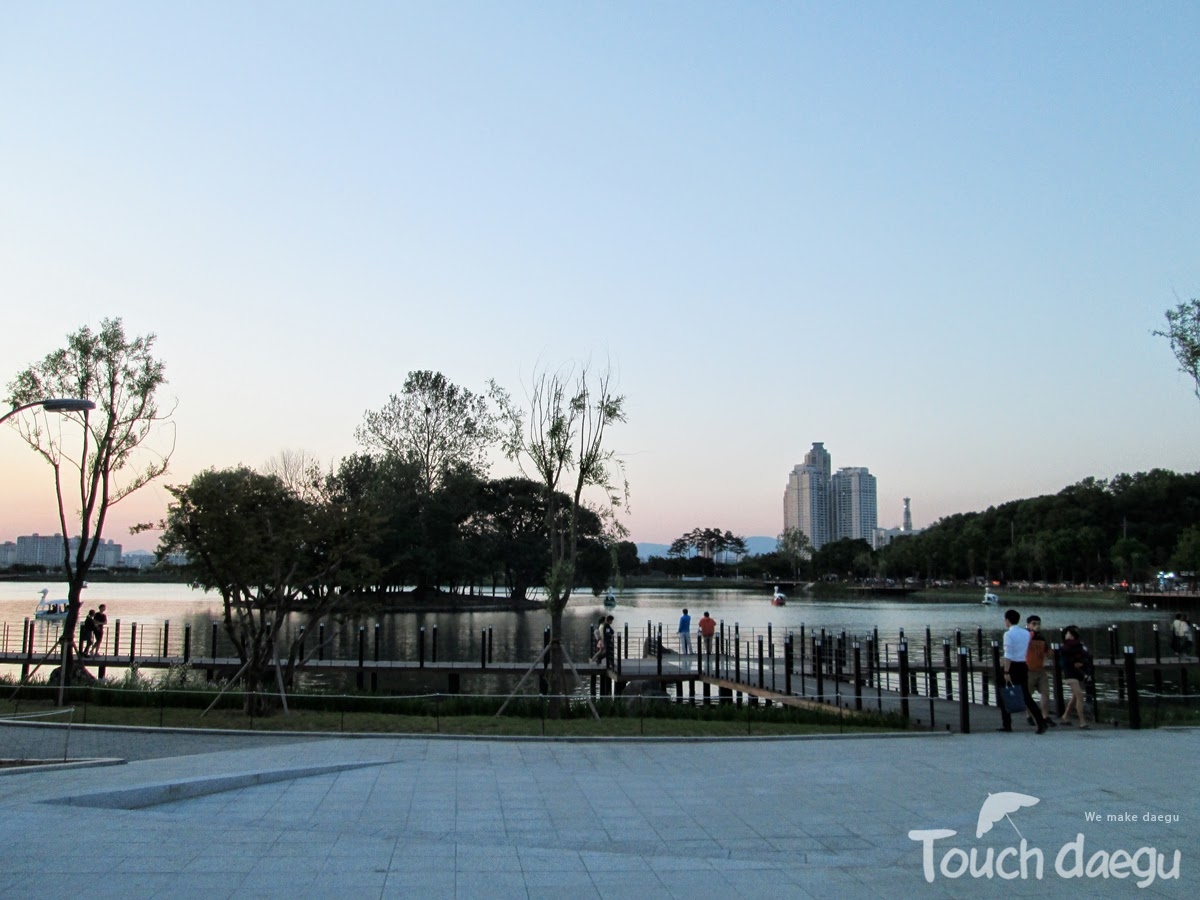 People are walking along the pedestrian paths in Suseong Lake
