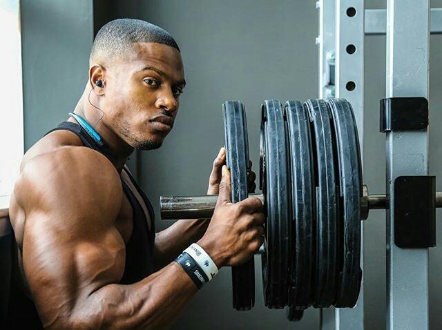 Hombre en el gimnasio cargando una barra con discos